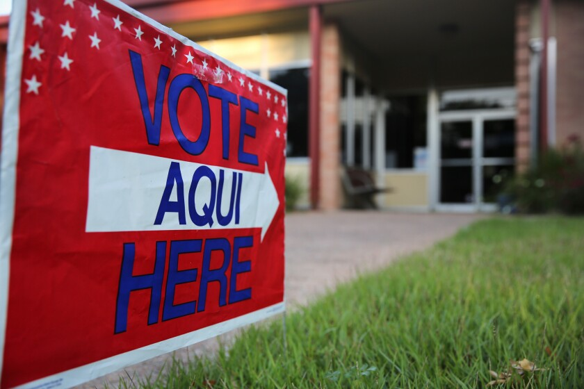 A bilingual sign stands outside a polling center in Austin, Texas. In California, where Latinos now outnumber whites, low voter turnout results in underrepresentation of Latino elected officials in all levels of government, according to a study.