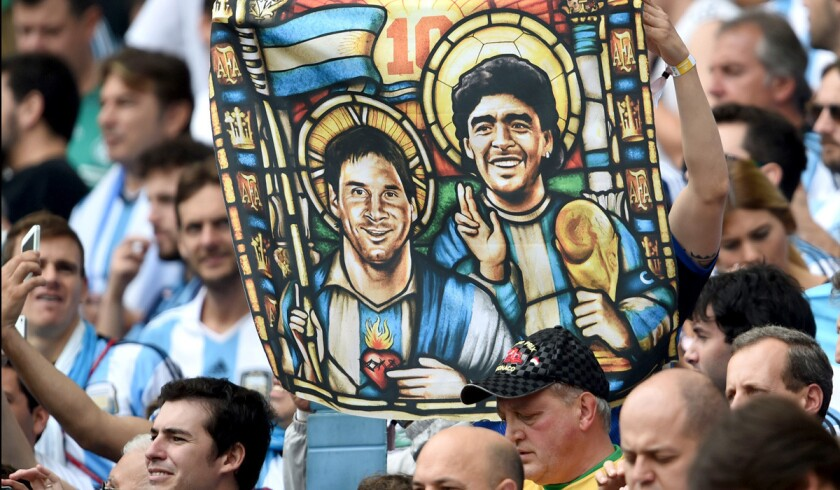 An Argentina fan holds an image depicting national team forward Lionel Messi and former World Cup star Diego Maradona as saints before a group game against Nigeria last week in Brazil.