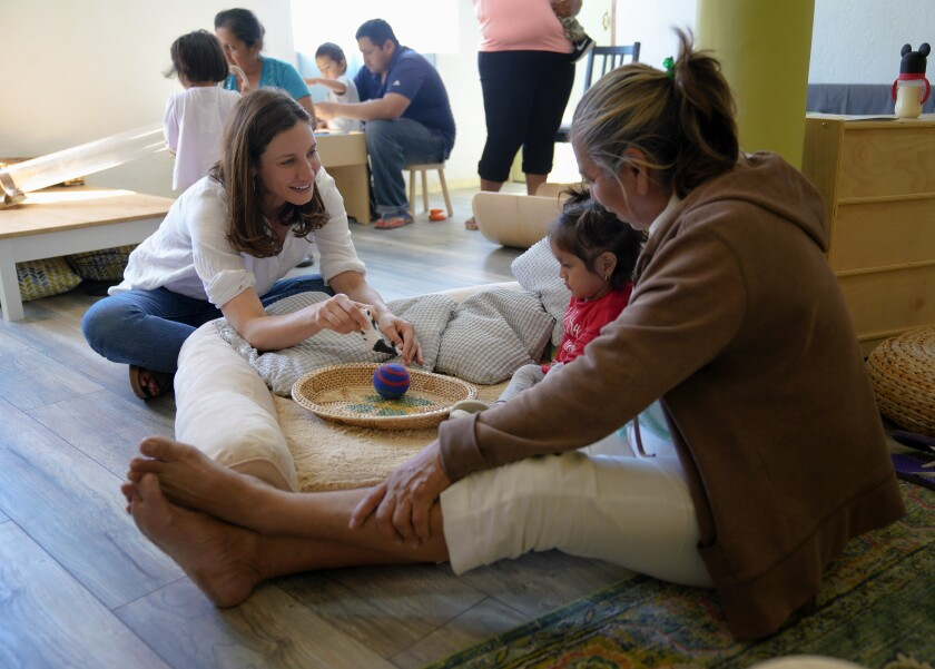 At a converted home in Tijuana, Mexico that is now used as a daycare for children whose families are seeking asylum in the United States, Lindsay Weissert interacts with Paulette, 1 1/2 and her grandmother, Graciela 60 who are at the daycare facility on September 9, 2019.