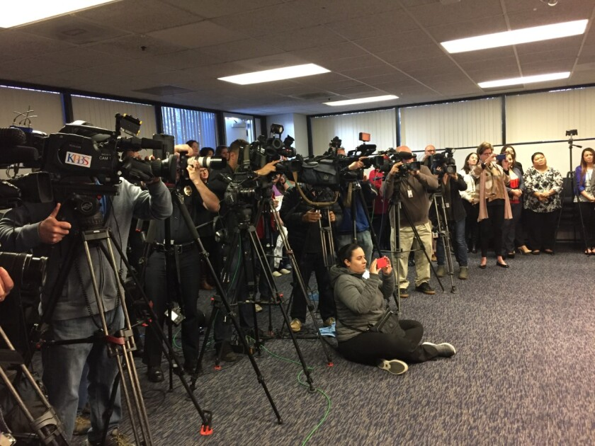 Alexandra Mendoza (seated) takes a photo at a San Diego Police Department headquarters press conference in 2018.
