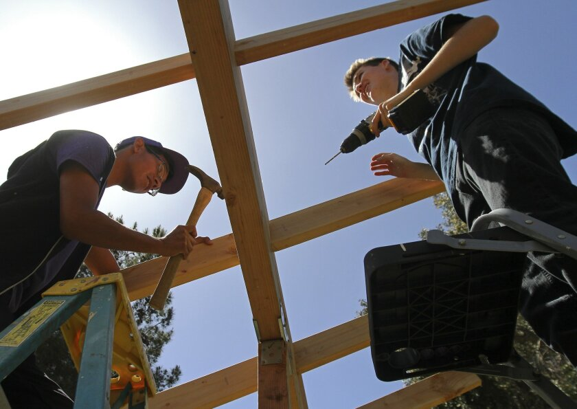 Brian Rivas, 17, and James Nix, 17, attach beams to a roof for their solar panel class at Rancho Vista High School in Temecula.