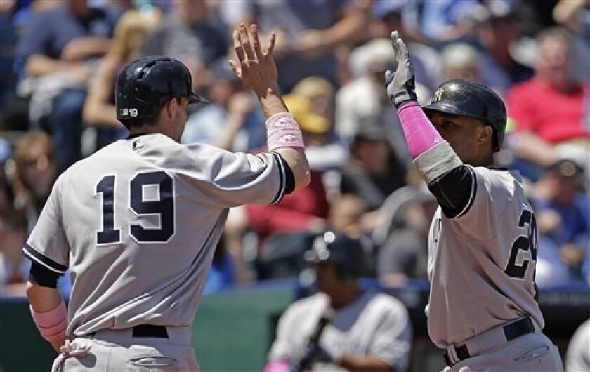New York Yankees' Robinson Cano, right, celebrates with teammate Chris Stewart (19) after hitting a two-run home run during the third inning of a baseball game against the Kansas City Royals, Sunday, May 12, 2013, in Kansas City, Mo. (AP Photo/Charlie Riedel)