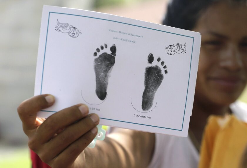 A woman in the country illegally shows the footprints of her baby daughter, who was born in Texas but has been denied a birth certificate.
