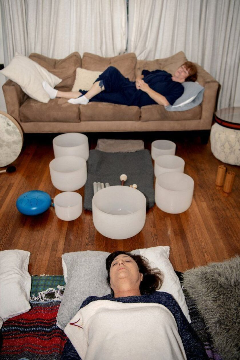 Eileen Klauber (top) and Linda Fenton get comfortable as the two prepare for the sound bath at Heim's home.