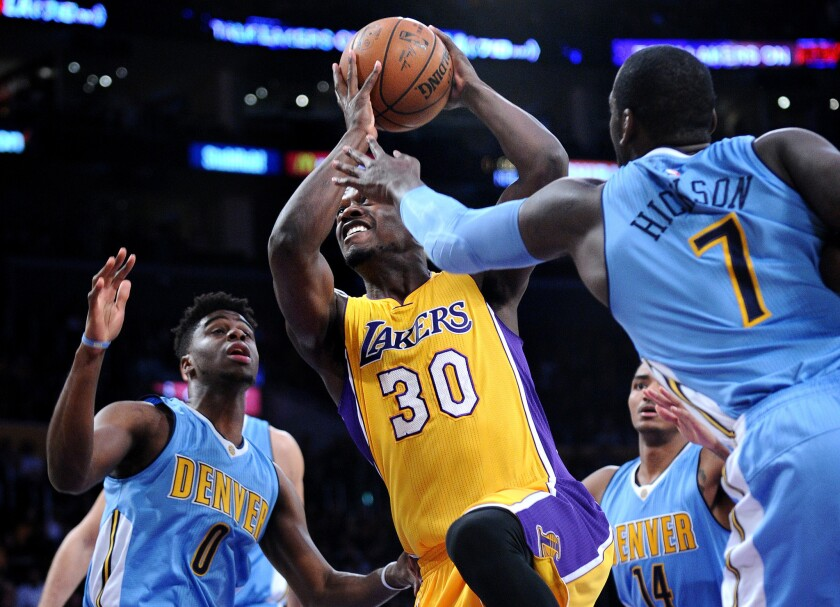 Lakers forward Julius Randle drives between Nuggets Emmanuel Mudiay, left, and J.J. Hickson during the first quarter of a game against Denver at Staples Center on Nov. 3.