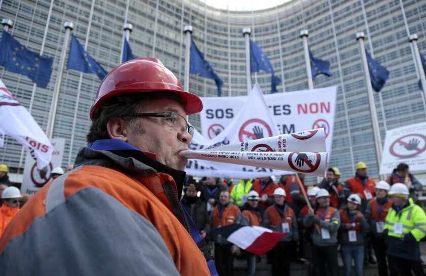 A steelworkers blows a paper horn during a demonstration of steelworkers in the European quarter of Brussels on Monday, Feb. 15, 2016. Thousands of steel workers from across the European Union demonstrated against the import of cheap Chinese products and warned EU leaders not to acerbate the situat