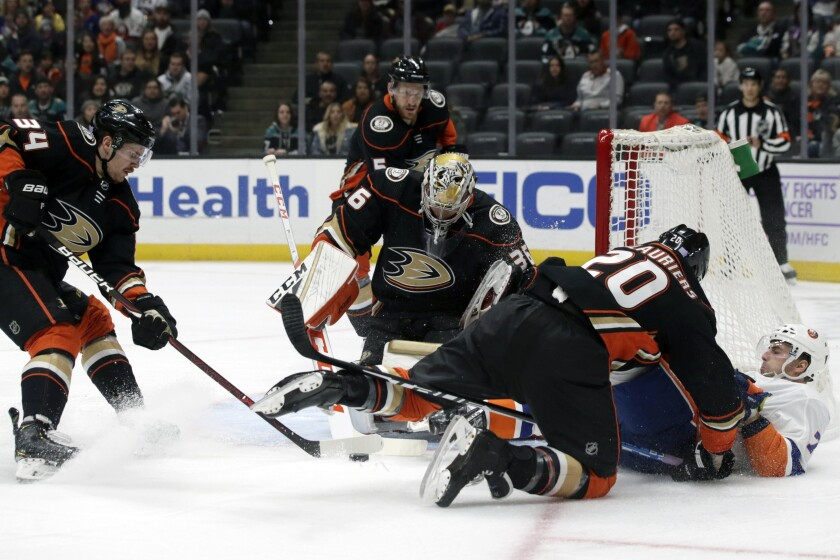 Islanders center Jordan Eberle gets hit to the ice by Ducks left wing Nicolas Deslauriers in front of goaltender John Gibson and center Sam Steelduring the first period of a game Nov. 25 at Honda Center.