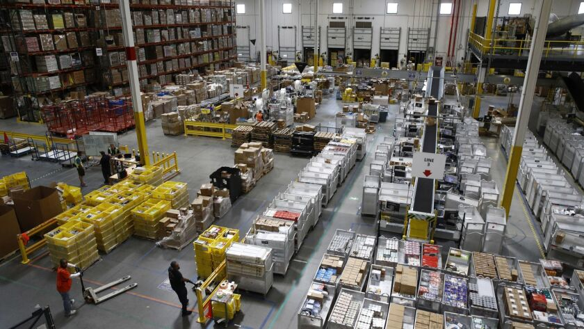 FILE- In this Aug. 3, 2017, file photo, workers prepare to move products at an Amazon fulfillment ce