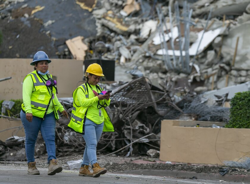 A workers make her way past the rubble and debris of the Champlain Towers South condo in Surfside, Florida on Tuesday, July 6, 2021. The rubble shown here is from the front portion of the condo towers, which was demolished 11 days after the back part of the tower collapsed with people inside. (Matias J. Ocner/Miami Herald via AP)