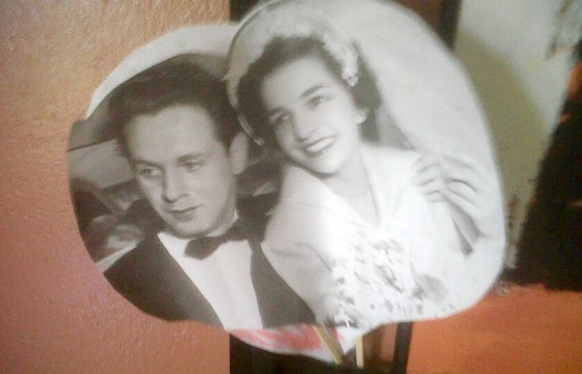 A photo of Tony and Grace Lopez on their wedding day, taped on the wall over Tony's bed in a nursing home.