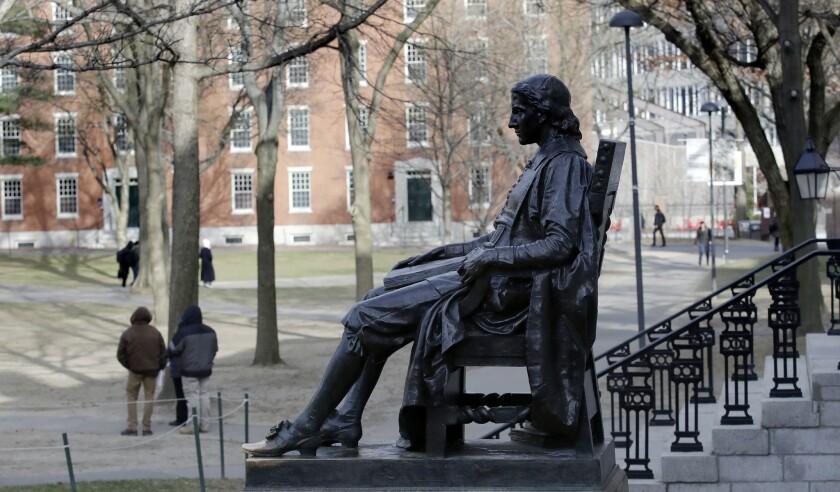 FILE - In this Dec. 13, 2018 file photo, the John Harvard statue looks over Harvard Yard at Harvard