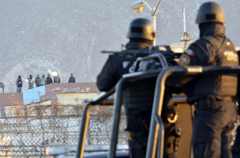 Presos se ubican en el tejado de la prisión de Topo Chico mientras la policía hace guardia en los perímetros después de una revuelta en Monterrey, México.