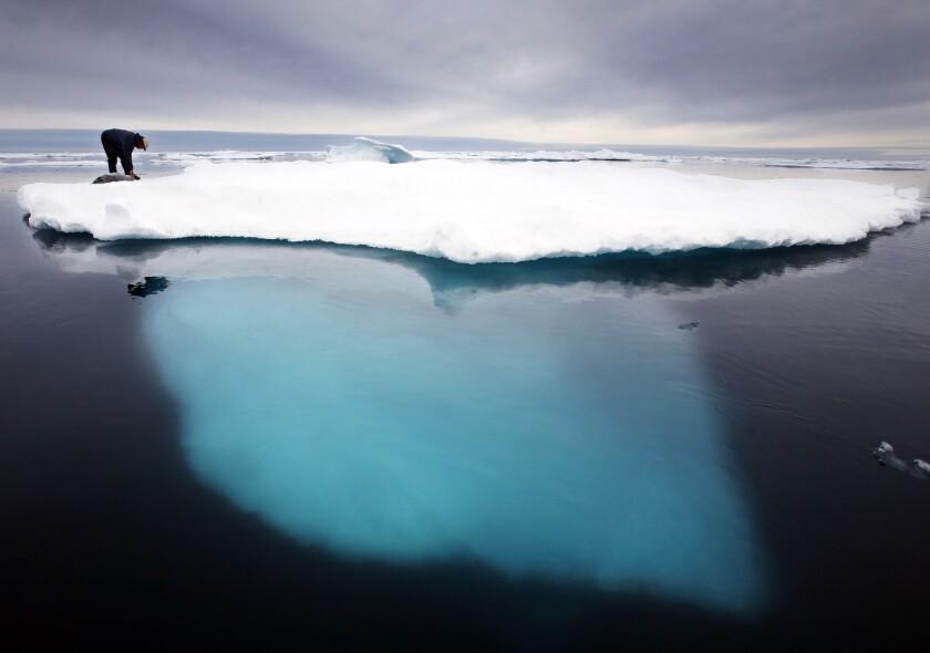 Inuit seal hunter atop a melting iceberg