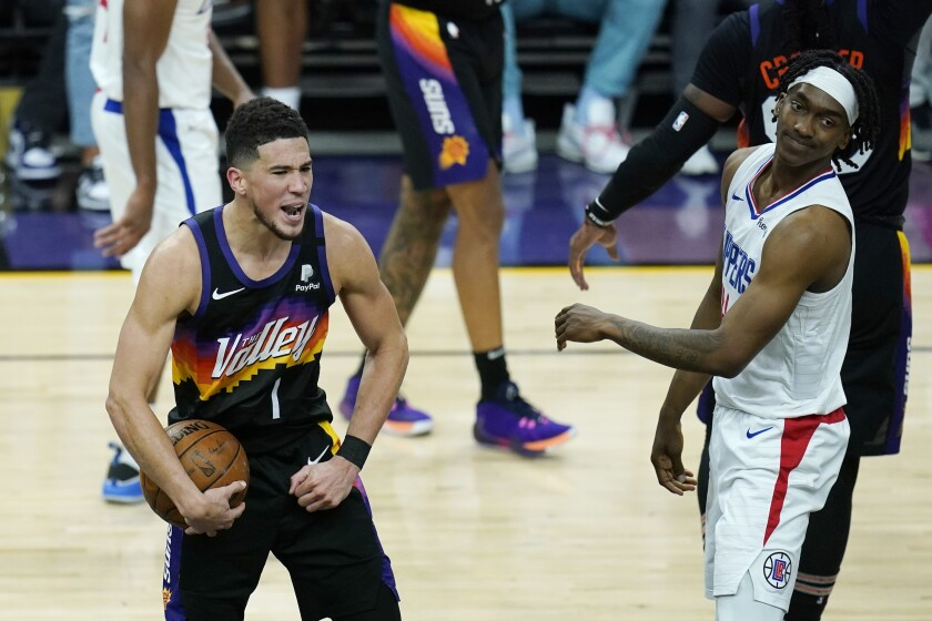 Phoenix Suns guard Devin Booker (1) celebrates near the end of the second half of Game 1 of the NBA basketball Western Conference finals as Los Angeles Clippers guard Terance Mann, right, looks on Sunday, June 20, 2021, in Phoenix. (AP Photo/Ross D. Franklin)