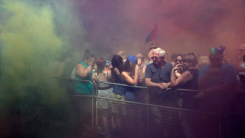 Spectators cover their faces after colorful smoke grenades were set off by members of the Black Lives Matters movement at the annual Pride Parade in Toronto on July 3.