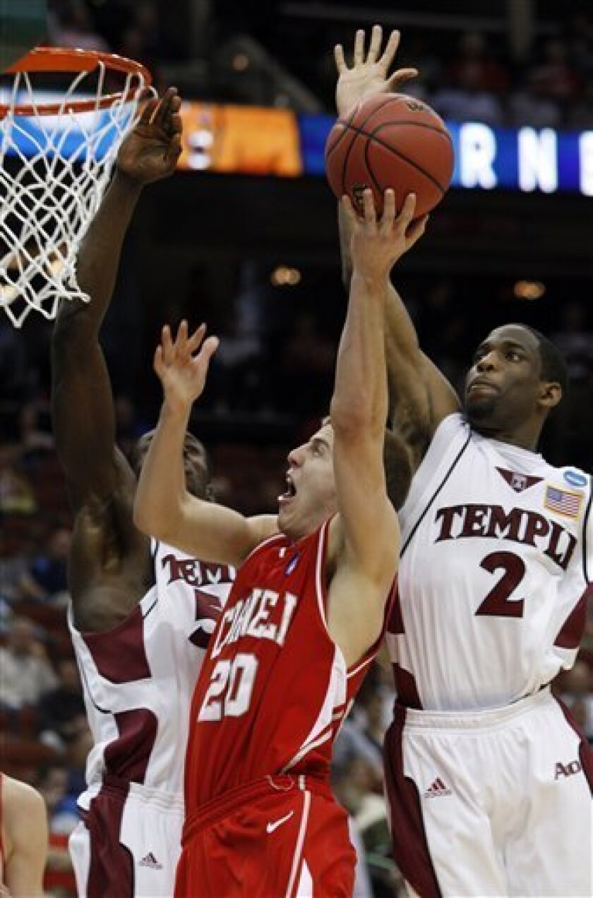 Cornell's Ryan Wittman (20) goes for a basket at Temple's Ryan Brooks (2) and Micheal Eric defend during an NCAA first-round college basketball game in Jacksonville, Fla., Friday, March 19, 2010.  (AP Photo/Steve Helber)