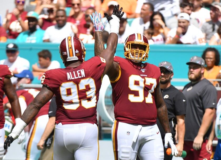 Washington Redskins teammates Tim Settle, right, and Jonathan Allen celebrate after sacking Miami Dolphins quarterback Josh Rosen on Sunday.