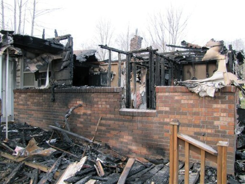 This photo shows the charred remains of  a home after a fire erupted, Saturday, March 9, 2013 in Gray, Ky. Fire erupted Saturday at a rural Kentucky home, killing two adults and five children inside, a coroner said. Knox County Coroner Mike Blevins said Saturday afternoon that the adult victims fou
