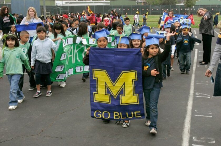 Diana Rivera (right, waving) leads teacher Priscilla Neri's first-grade class, representing the University of Michigan. Each class has adopted a different college.