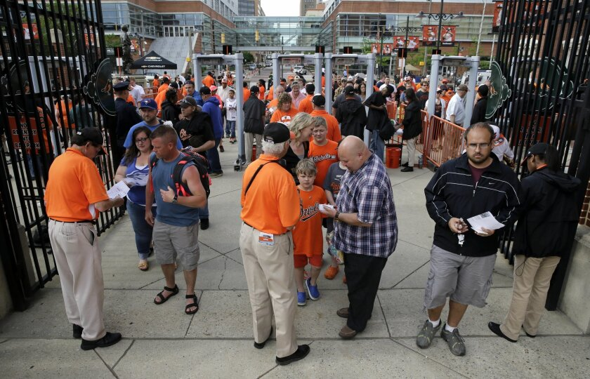 Ushers check fans' tickets as they enter Orioles Park at Camden Yards before a baseball game between the Baltimore Orioles and the Toronto Blue Jays, Monday, May 11, 2015, in Baltimore. Playing in front of their home fans for the first time in two weeks, the struggling Orioles hope a game at Camden