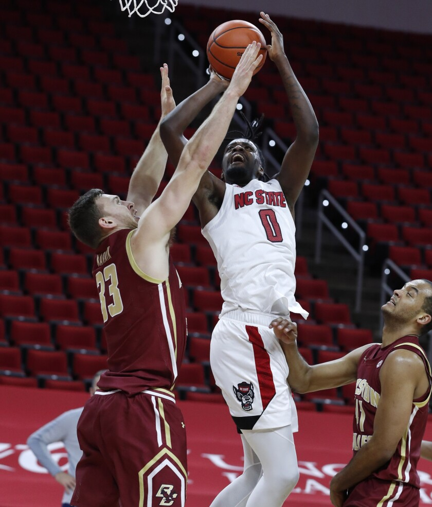 North Carolina State's D.J. Funderburk (0) shoots as Boston College's James Karnik (33) defends during the first half of an NCAA college basketball game in Raleigh, N.C., Wednesday, Dec. 30, 2020. (Ethan Hyman/The News & Observer via AP, Pool)