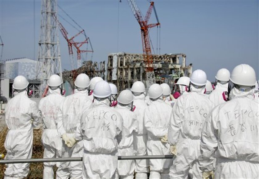 Members of the media, wearing protective suits and masks, visit the Unit 3 and Unit 4 reactor buildings of tsunami-crippled Fukushima Dai-ichi nuclear power station of Tokyo Electric Power Co., during a press tour escorted by TEPCO officials, in Okuma, Fukushima prefecture, northeastern Japan,  Tue