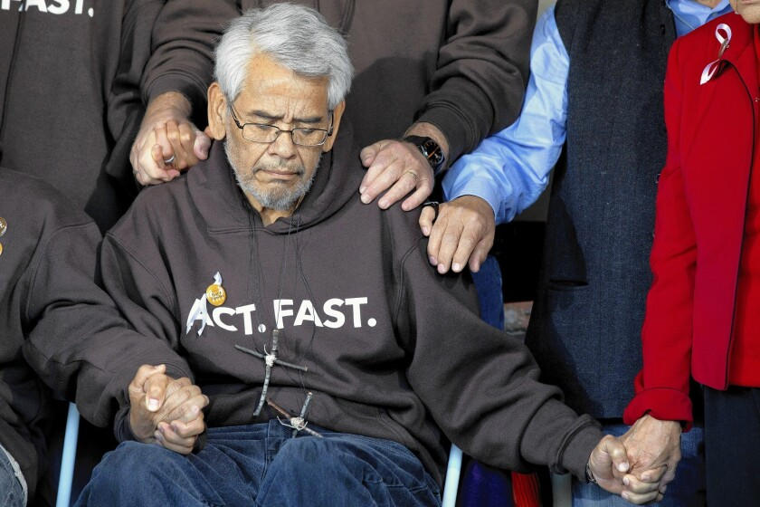 Eliseo Medina holds hands during a prayer at an event ending his 2013 fast after 22 days. He is heading to Washington, D.C., to lead another protest for immigration reform.