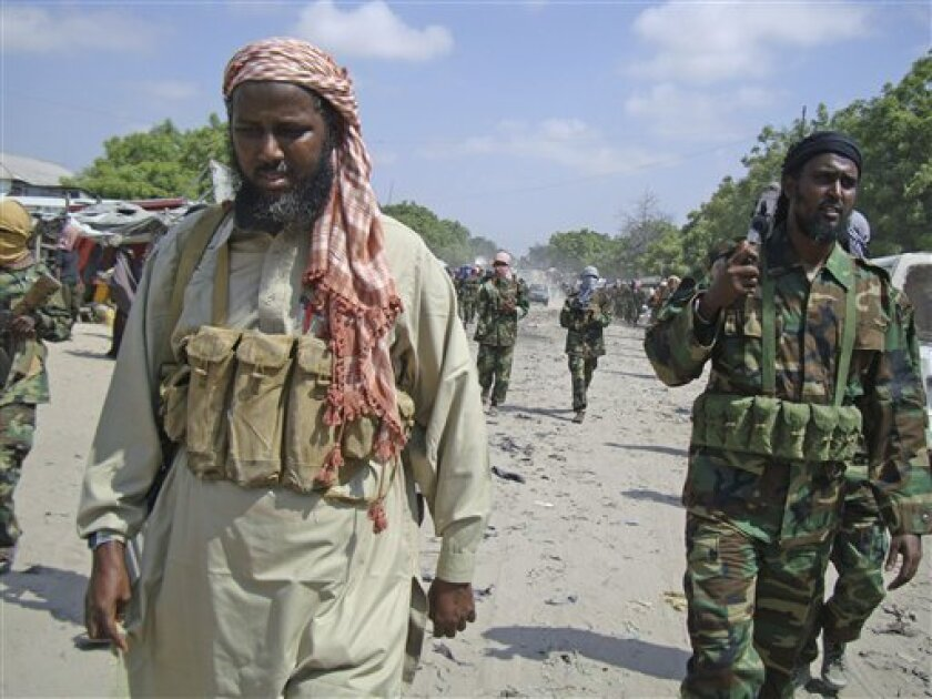 In this Jan. 1, 2010 photo, Sheik Mukhtar Robow, also known as Abu Mansur, the deputy leader of al-Shabab, left, is flanked by the group's spokesman Sheik Ali Mohamud Rage, right. Ugandan police, with help from the FBI and Kenyan police, have arrested 36 people from seven countries in connection with the twin bombings during July's World Cup finals, that rocked Uganda's capital, killing 76 people. At least one suspect said he was recruited and trained by al-Qaida. The Somali militant group that claimed responsibility for the blast, al-Shabab, has known links with the international terror group. A day after the blasts, al-Shabab, Somalia's most powerful militant group, said the bombings were retaliation for Ugandan troops' participation in the African Union peacekeeping mission in Mogadishu. The militant group promised more attacks, a threat Ugandan officials take seriously. (AP Photo/Farah Abdi Warsameh)