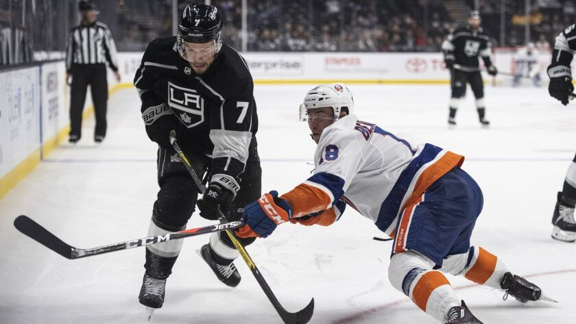 Kings defenseman Oscar Fantenberg, left, and New York Islanders center Anthony Beauvillier battle for the puck in the third periodon Oct. 18, 2018 in Los Angeles.