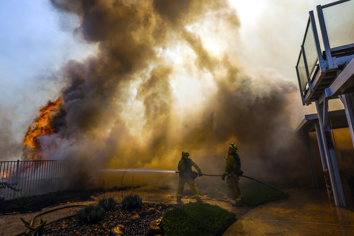 MURRIETA, CA - SEPTEMBER 05, 2019 — Firefighters work in heavy smoke and flames to protect a structure on Silverewood Street in Murrieta. Tenaja fire continues rage in Murrieta on Thursday. A fast-moving fire erupted in hillside terrain near Murrieta on Wednesday night, quickly scorching almost 1,000 acres and prompting mandatory evacuation orders for multiple residential enclaves as fire officials urged others nearby to voluntarily leave. (Irfan Khan/Los Angeles Times)