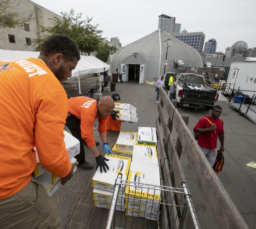 From left, Joseph French, Paul Simonton and Sergio Contreras Jr. load supplies from a city-funded homeless bridge shelter to take them to the convention center on Tuesday.