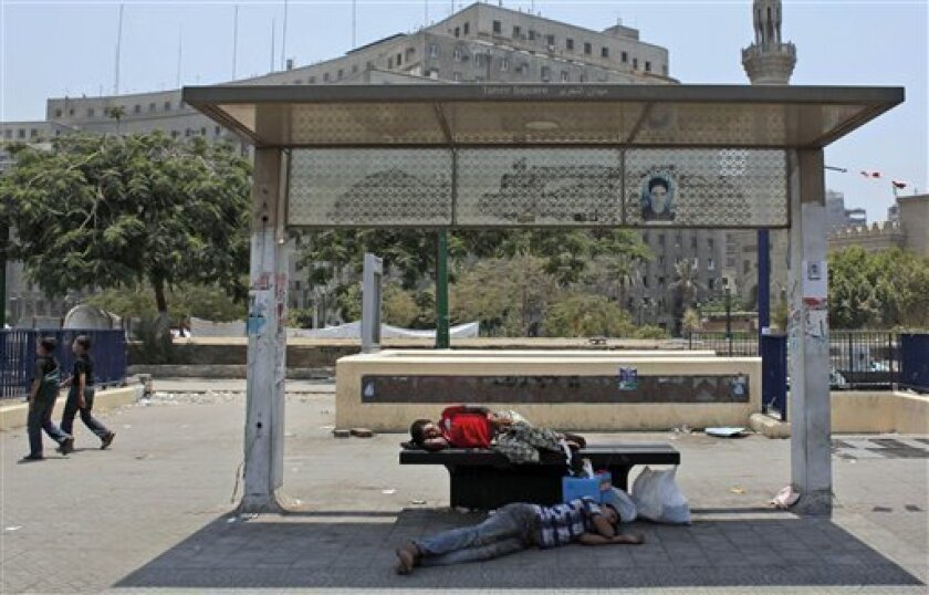 Two Egyptian youths take a nab at a bus stop in Tahrir Square as demonstrators are still camping out for the fourth day, in Cairo, Egypt Monday, July 11, 2011. Egypt's benchmark stock index dropped by more than 2.6 percent Monday, dragged down by concerns of mounting unrest in the Arab world's most populous nation. (AP Photo/Nasser Nasser)