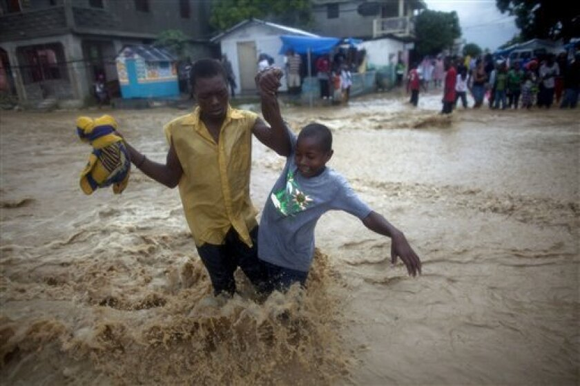 People wade through a flooded street during the passing of Hurricane Tomas in Leogane, Haiti, Friday Nov. 5, 2010. (AP Photo/Ramon Espinosa)