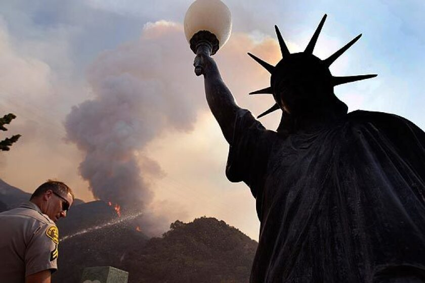 A Los Angeles County sheriff's deputy stands near a facsimile of the Statue of Liberty in La Crescenta.