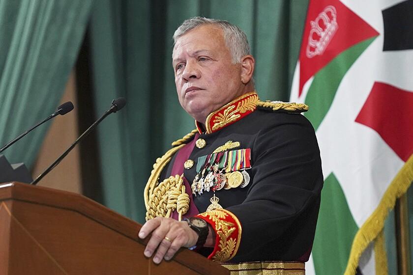 Jordan's King Abdullah II at a lectern with a flag behind him.