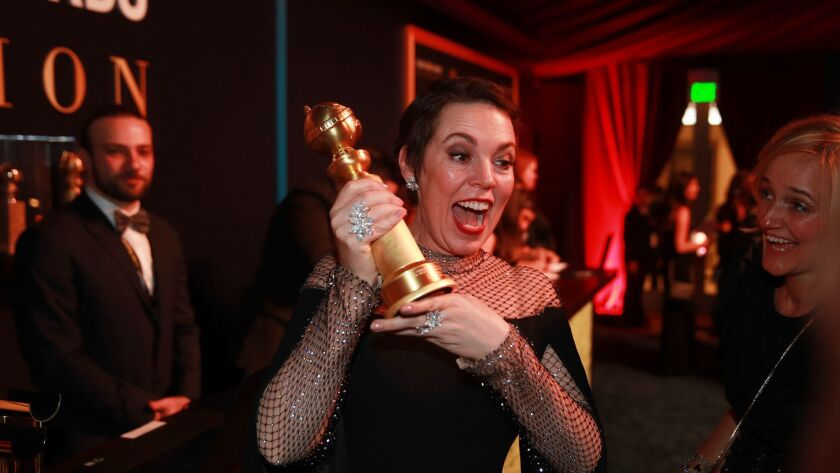"""Olivia Colman holds up her Golden Globe for best actress, musical or comedy for """"The Favourite"""" hours after her victory."""