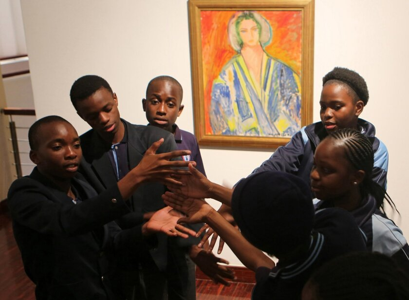 In this photo taken Wednesday Aug. 24, 2016, students from the New Model School pose for a photo in front of a work by artist Henri Matisse in Johannesburg. For the first time, Africa is hosting an exhibit devoted to Henri Matisse. The show in Johannesburg features more than 80 works, including a p