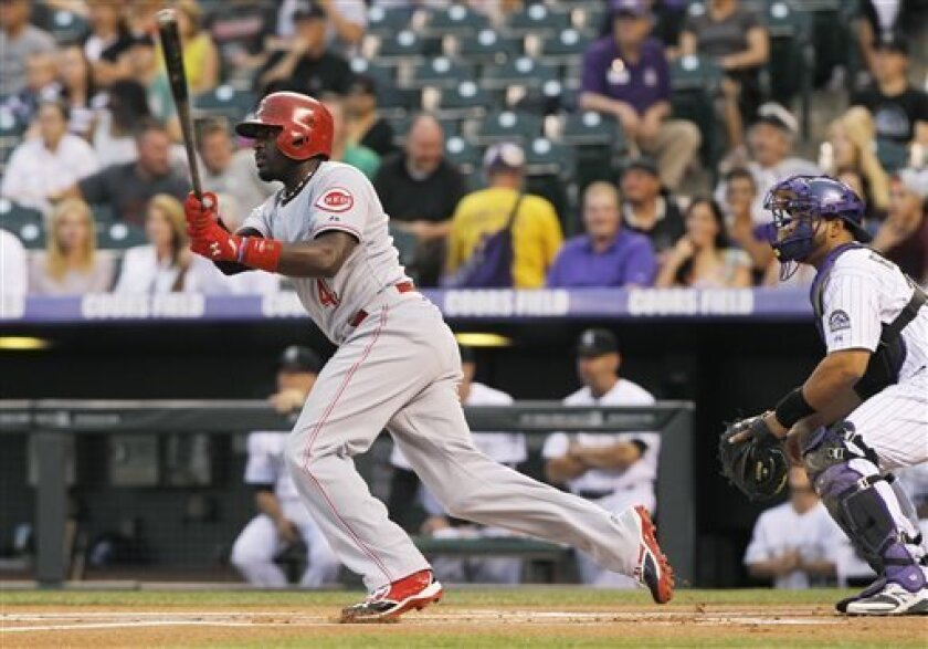 Cincinnati Reds' Brandon Phillips, left, follows the flight of his RBI-triple with Colorado Rockies catcher Wilin Rosario in the first inning of a baseball game in Denver on Saturday, Aug. 31, 2013. (AP Photo/David Zalubowski)