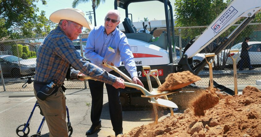 Robert Bettinger, left, and William E. Kelly took turns tossing dirt during the groundbreaking ceremony for a planned LGBT-affirming senior community they hope to live in when it's built next year. — Peggy Peattie