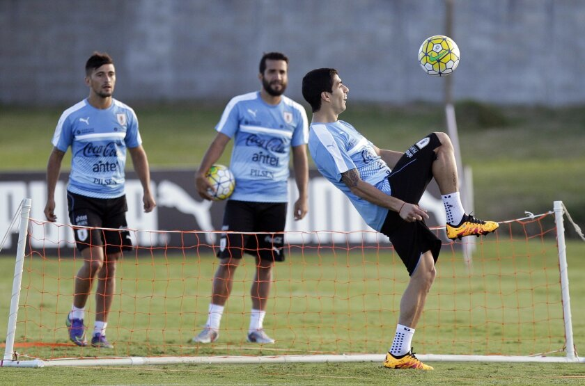 Luis Suarez controls the ball as teammates Giorgian De Arrascaeta, left, and Mauricio Victorino watch during a training session in Montevideo, Uruguay, Monday, March 21, 2016. Uruguay will face Brazil in a 2018 World Cup qualifying soccer match on March 25. (AP Photo/Matilde Campodonico)