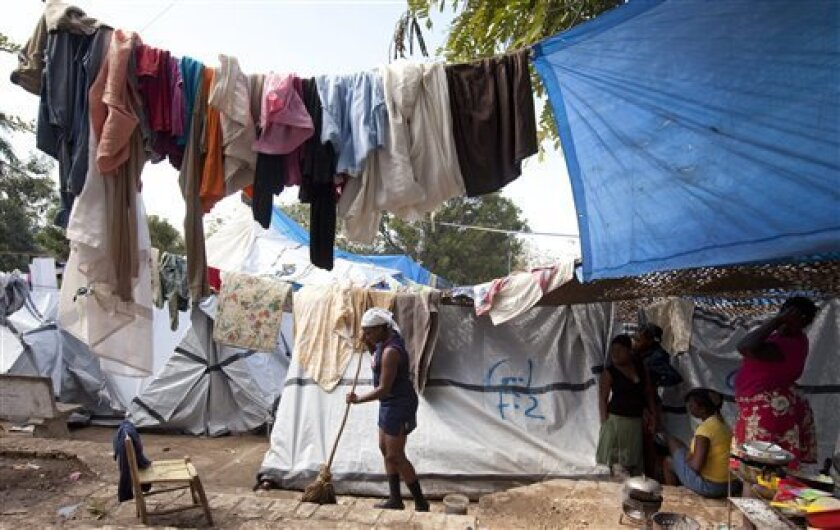 A woman sweeps the outside of a tent in a displaced person camp, Sunday, March 7, 2010, in Port-au-Prince, Haiti. Canadian Gov. Gen. Michaelle Jean arrives Monday for a two-day visit of her home country for her first visit since the devastating earthquake. (AP Photo/The Canadian Press, Paul Chiasso