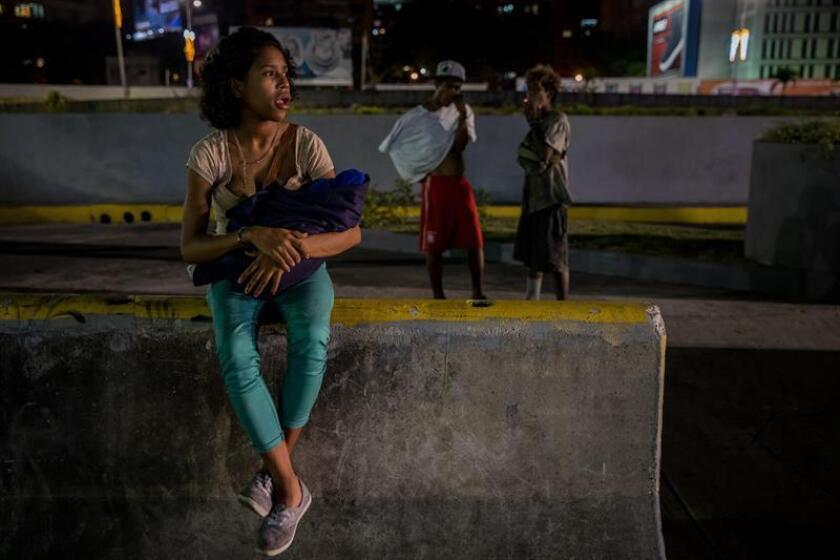 Liliana, 17, holds her newborn baby Angel, with friends Gabriel and Jose Angel seen in the background - they are among the many youngsters living on the streets of Caracas who bathe in dirty rivers and hunt for food in garbage cans, and are yet another aspect of the severe social and economic crisis gripping oil-producing Venezuela. EFE-EPA/Miguel Gutierrez