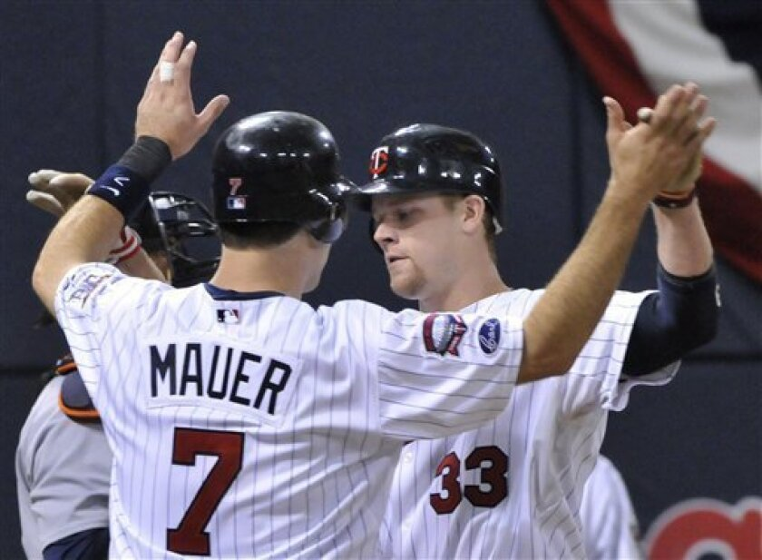 Minnesota Twins' Joe Mauer, left, welcomes Justin Morneau after Morneau's two-run home run off Detroit Tigers' Rick Porcello in the fourth inning of a baseball game Sunday, July 5, 2009 in Minneapolis. (AP Photo/Jim Mone)