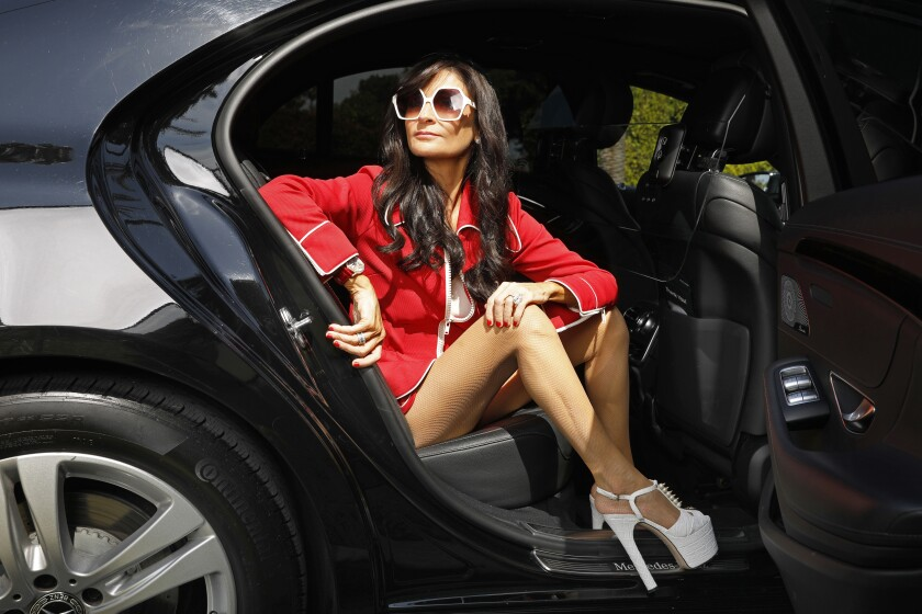 A woman in a scarlet blazer and white platform heels steps out of a luxury car