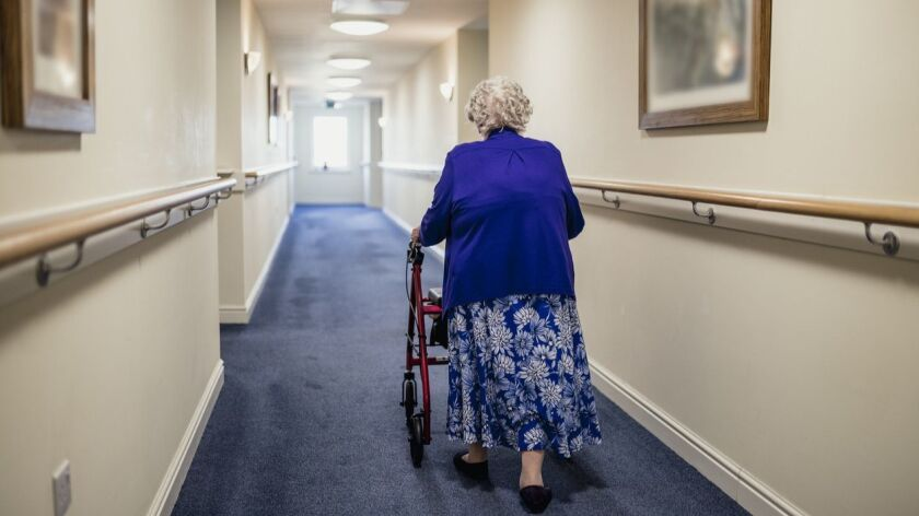 A senior woman walking down a corridor with the assistance of a walker.
