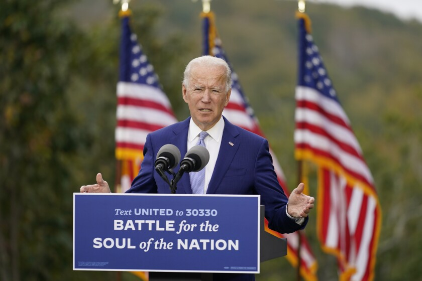 """Joe Biden campaigns outside in Warm Springs, Ga., with a sign reading: """"Battle for the soul of the nation."""""""