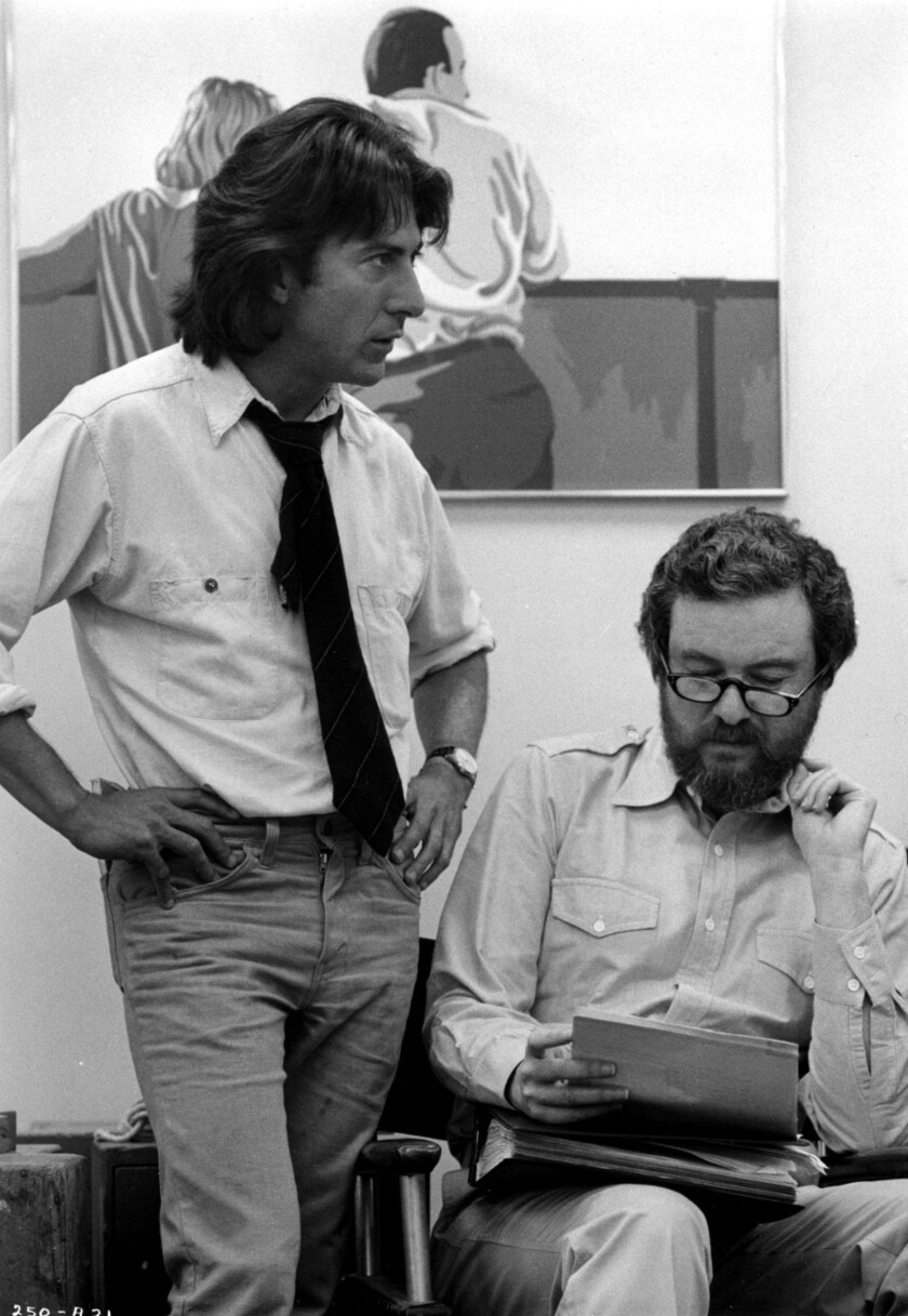 "Black-and-white shot of Dustin Hoffman, left and standing, and Alan Pakula, seated, on the set of ""All the President's Men"" in 1976."