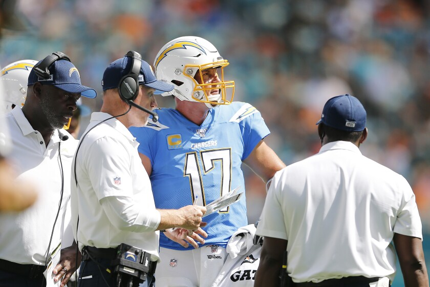 Chargers coach Anthony Lynn, left, and offensive coordinator Ken Whisenhunt, center, speak with quarterback Philip Rivers.