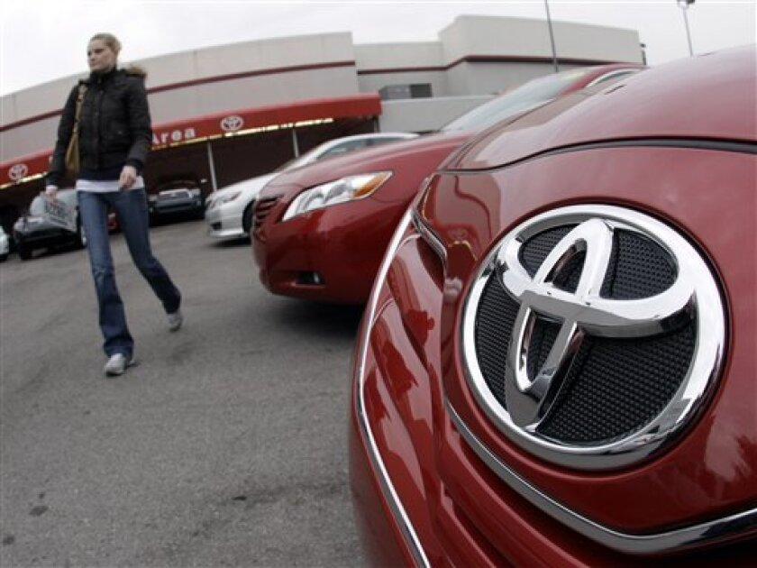 A customer walks past a new 2010 Toyota Camry at a dealership on Wednesday, Jan. 27, 2010 in Nashville, Tenn. Toyota Motor Corp. announced late Tuesday it would halt sales of some of its top-selling models to fix gas pedals that could stick and cause unintended acceleration. (AP Photo/Mark Humphrey)
