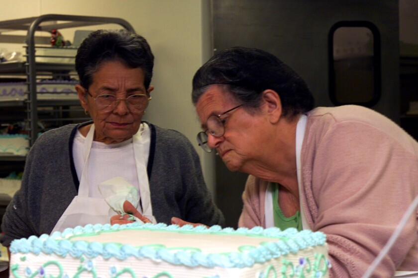 In a photo from 2001, Rosa Porto decorates a cake as Urvicia Garcia watches. Porto, who began selling cakes from her home in Cuba over 50 years ago, died Friday at age 89.
